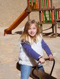 Het blonde kindmeisje spelen in speelplaats die op schommeling glimlachen Royalty-vrije Stock Afbeelding
