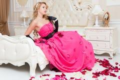 Het blonde in lange rode kleding zit op het bed met rozen royalty-vrije stock afbeeldingen