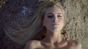 Het blonde ligt op een steen stock footage