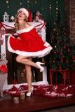 Het blonde meisje draagt Kerstmankostuum, die naast Kerstboom en schoorsteen stellen stock afbeeldingen