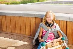 Het blonde meisje draagt sweatshirt over schouders het zitten Royalty-vrije Stock Foto