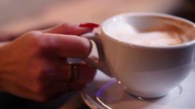 Het blonde meisje drinkt koffie en het babbelen in de telefoon, zittend op een beige laag in 4k resolutie in langzame motie stock footage