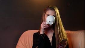 Het blonde meisje drinkt koffie en het babbelen in de telefoon, zittend op een beige laag in 4k resolutie in langzame motie stock videobeelden
