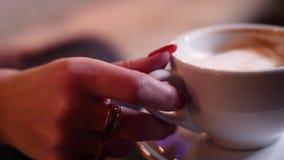 Het blonde meisje drinkt koffie en het babbelen in de telefoon, zittend op een beige laag in 4k resolutie in langzame motie stock video