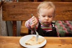 Het blonde meisje eet pannekoeken royalty-vrije stock afbeelding