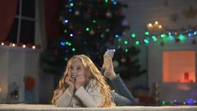 Het blonde meisje liggen op vloer die over Kerstmisviering denken, die wachten op stelt voor stock footage