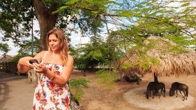 Het blonde Meisje maakt Selfie tegen Antilopen in Dierentuin Openluchtkooi stock videobeelden