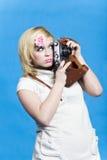 Het blonde meisje met retro camera kijkt opzij Stock Afbeeldingen