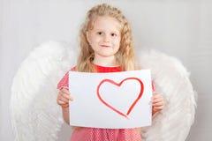 Het blonde meisje met vleugels van een engel in de kaart van de Dag van een Valentijnskaart Stock Foto's