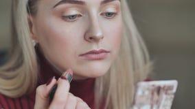 Het blonde meisje schildert haar lippen met lippenstift met een saaie rode kleur stock videobeelden