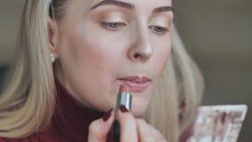 Het blonde meisje schildert haar lippen met lippenstift met een saaie rode kleur stock footage