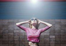 Het blonde meisje stellen in roze gestreepte blouse en zonglazen, omhoog kijkend met terug geworpen hoofd en handen Dag, openluch Royalty-vrije Stock Afbeelding