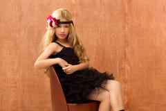 Het blonde meisje van het fashinjonge geitje op retro uitstekende zetel royalty-vrije stock foto's