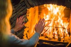 Het blonde meisje verwarmt haar handen door de brand in de open haard Comfortabele de winteratmosfeer dichtbij de open haard stock foto's