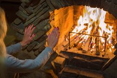 Het blonde meisje verwarmt haar handen door de brand in de open haard Comfortabele de winteratmosfeer dichtbij de open haard stock fotografie