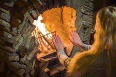 Het blonde meisje verwarmt haar handen door de brand in de open haard Comfortabele de winteratmosfeer dichtbij de open haard stock afbeelding
