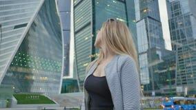 Het blonde meisje verzendt een luchtkus naar de camera op de achtergrond van wolkenkrabbers en high-rise gebouwen van de stad stock video