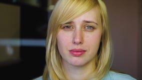Het blonde met verschillende ogen bekijkt de camera en verwijdert haar hand, heterochromia, in langzame motie stock video