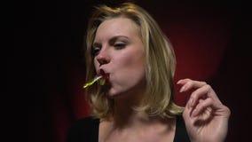 Het blonde vulde in de mond van geleiwormen en kauwt, vertraagt motie stock video