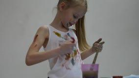 Het blonde weinig schoolmeisjeschilder trekt op zich en haar kleren Langzame Motie stock videobeelden