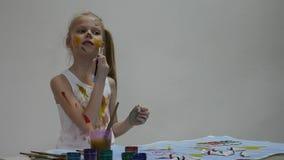 Het blonde weinig schoolmeisjeschilder trekt op zich en haar kleren Langzame Motie stock video