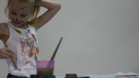 Het blonde weinig schoolmeisjeschilder trekt op zich en haar kleren Langzame Motie stock footage