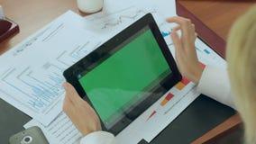Het blonde werkt in een bureau met de tablet met stock video