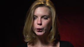 Het blonde zuigt in een rode geleiworm, beet langzame motie stock footage