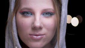 Het blondekereltje in hoodie met kleurrijke samenstellingsdraaien van linkerzijde aan het recht en glimlacht onhandig op vage lic stock video