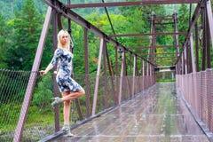 Het blondemeisje bevindt zich op een brug die van metaal en hout wordt geconstrueerd stock fotografie