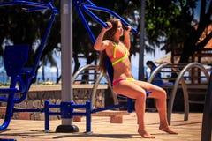 Het blondemeisje in bikini zit op de simulator van de gewichtsstapel dichtbij strand Royalty-vrije Stock Foto's