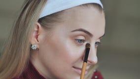 Het blondemeisje doet haar eigen oogmake-up stock video