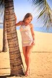 het blondemeisje in kantclose-up leunt op palmboomstam op strand Royalty-vrije Stock Fotografie