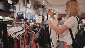 Het blondemeisje kiest dingen in de de kledingsopslag van de vrouwen stock videobeelden