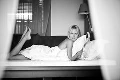 Het blondemeisje ligt in bed in de ochtend Royalty-vrije Stock Foto's