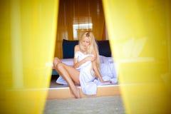 Het blondemeisje ligt in bed in de ochtend Stock Afbeeldingen