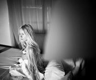 Het blondemeisje ligt in bed in de ochtend Stock Foto