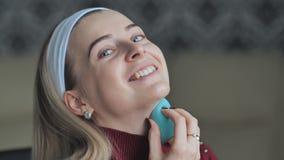 Het blondemeisje past camouflagestift met een spons op haar gezicht vóór samenstelling toe stock video