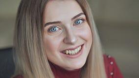 Het blondemeisje pronkt met haar lichte make-up terwijl het glimlachen stock footage