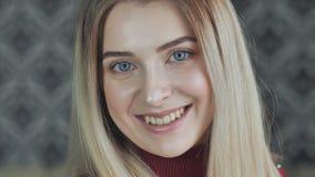 Het blondemeisje pronkt met haar lichte make-up terwijl het glimlachen stock video