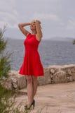 het blondemeisje in rode kleding bevindt zich dichtbij van het overzees Stock Foto