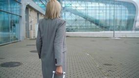 Het blondemeisje rolt een koffer dichtbij de luchthaventerminal - bekijk van de rug Langzame Motie stock footage