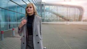 Het blondemeisje rolt een koffer dichtbij de luchthaventerminal Langzame Motie stock videobeelden