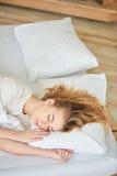 Het blondemeisje slaapt op wit bed stock fotografie
