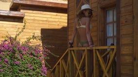 Het blondemeisje in strohoed en zwempak zit op de portiek stock footage