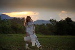 het blondemeisje in Vietnamese kleding kijkt neer op gebied Royalty-vrije Stock Afbeeldingen