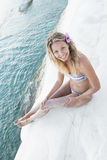 Het blondemeisje zit op een witte rots door het overzees Stock Foto's