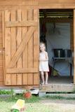 Het blootvoetse meisje in de zomer sundress bevindt zich in de deuropening van de loods royalty-vrije stock afbeelding