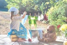 Het blootvoetse meisje die haar speelgoed wassen kleedt zich dichtbij waskom Stock Afbeeldingen