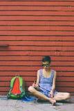 Het blootvoetse meisje trekt het zitten dichtbij een bakstenen muur royalty-vrije stock fotografie